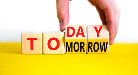 Do it today not tomorrow. Businessman turns wooden cubes and changes the word 'tomorrow' to 'today'. Beautiful yellow table, white background, copy space. Business and tomorrow or today concept. Stock Photo