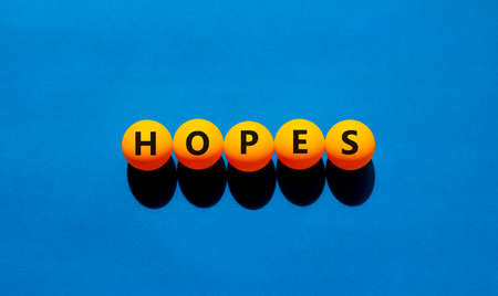 Hopes symbol. The concept word 'hopes' on orange table tennis balls. Beautiful blue table, blue background, copy space. Business, psychological and hope and hopes concept. Stock Photo