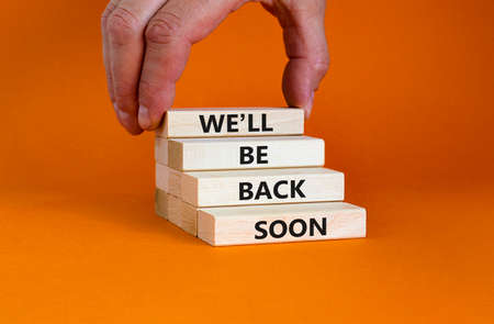 We will be back soon symbol. Concept words 'We will be back soon' on wooden blocks on a beautiful orange background. Businessman hand. Business, we will be back soon concept.