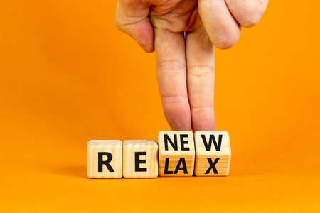 Relax and renew symbol. Businessman turns cubes and changes the word 'relax' to 'renew'. Beautiful orange table, orange background. Business, relax and renew concept. Copy space.