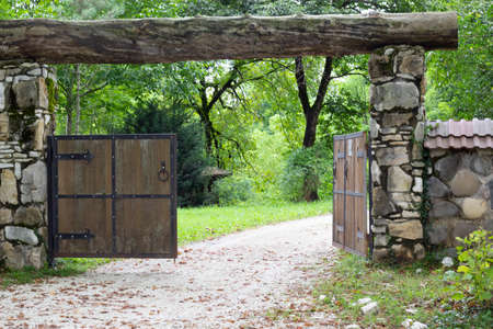 The wooden gate in a stone wall on a monastery. Retro countryside wooden gate with with stone wall in vintage style. Peaceful nature. Conceptual image.
