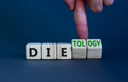 Dietology instead die symbol. Doctor turns wooden cubes and changes the word die to dietology. Beautiful grey table, grey background. Healthy lifestyle, dietology instead die concept. Copy space. Stock Photo