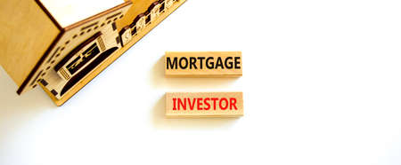 Mortgage investor symbol. Concept words 'Mortgage investor' on wooden blocks near miniature wooden house. Beautiful white background. Business, mortgage investor concept.