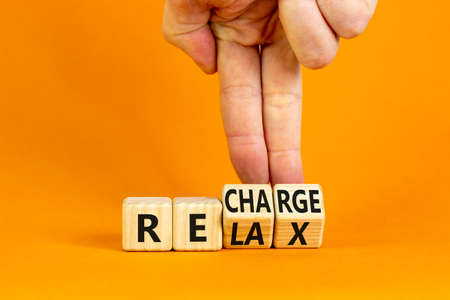 Relax and recharge symbol. Businessman turns cubes and changes the word 'relax' to 'recharge'. Beautiful orange table, orange background. Business, relax and recharge concept. Copy space.