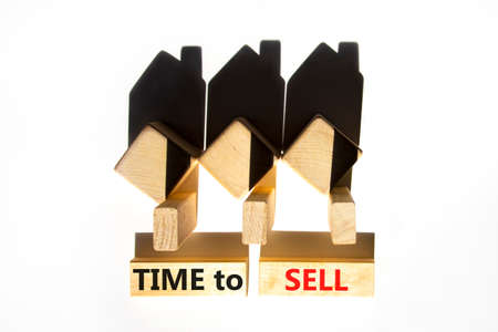 Time to sell house symbol. Concept words 'Time to sell' on wooden blocks near miniature houses from shadows. Beautiful white background, copy space. Business and time to sell house concept.
