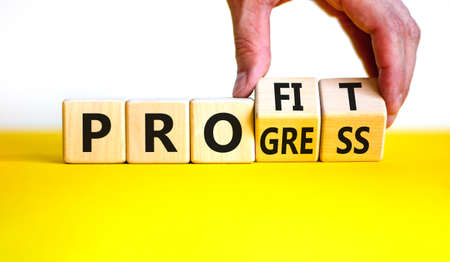 Progress and profit symbol. Businessman turns wooden cubes, changes the word 'progress' to 'profit'. Beautiful yellow table, white background. Business, progress and profit concept. Copy space.