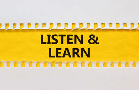 Listen and learn symbol. White and yellow paper with words 'Listen and learn'. Beautiful yellow background. Business, educational and listen and learn concept. Copy space. Stock Photo