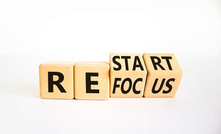 Refocus and restart symbol. Businessman turned cubes and changed the word 'refocus' to 'restart'. Beautiful white table, white background. Business refocus and restart concept. Copy space. Stock Photo