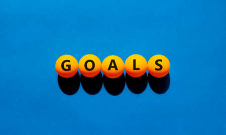 Goals symbol. The concept word 'goals' on orange table tennis balls. Beautiful blue table, blue background. Business and goals or goal concept. Stock Photo