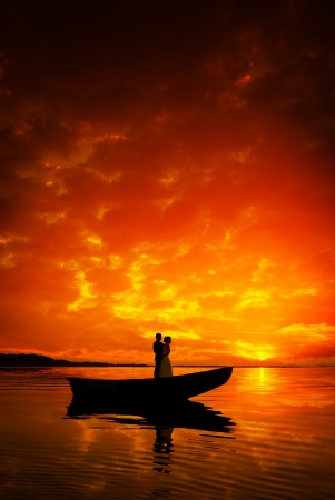Silhouette of a couple kissing in boat on river in sunset  photo