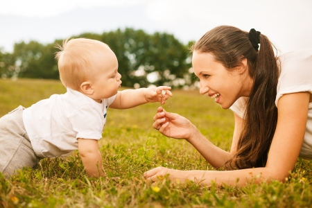 mother passing flower to her baby in the park photo