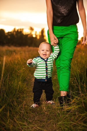 Very cute baby boy smiling and having fun with his mother outside, baby making first steps photo