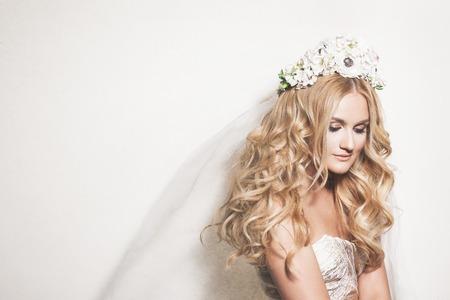 Portret van aanhankelijk blonde bruid. Bruiloft make-up en kapsel. Bruiloft decoratie Stockfoto