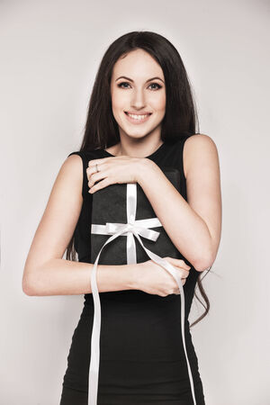 Young beautiful woman with long hair wearing black cocktail dress is holding elegantly wrapped gift. photo