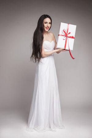 maxi dress: Young beautiful woman with long dark hair wearing maxi white dress, holding gift wrapped in white paper with red ribbon. Stock Photo
