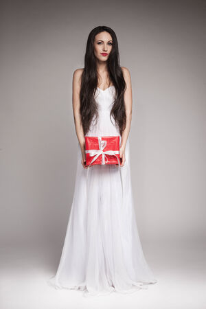 maxi: Young beautiful woman with long dark hair wearing maxi white dress, holding gift wrapped in red paper with  white ribbon.