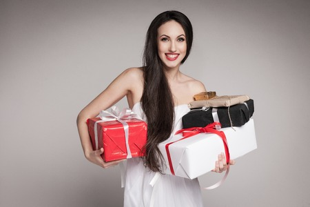 Young surprised woman holding multiple gifts. Beautiful elegant brunette carrying her presents. photo