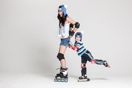 patinando: Apuesto familia, madre e hijo, que presenta en estudio vistiendo patines en l�nea y sombreros a juego divertido