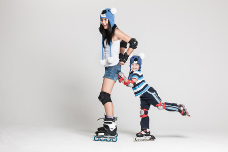 roller blade: Good looking family, mother and son, posing in studio wearing inline rollerskates and matching funny hats