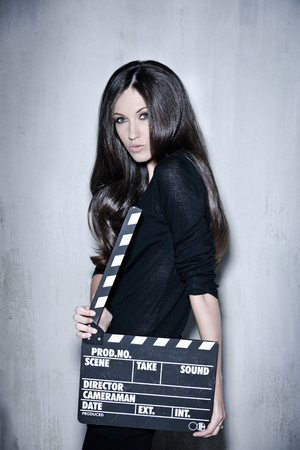 Sensuality beautiful woman with long hair, dressed in black posing in studio, holding clapperboard