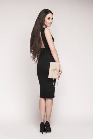 elegantly: Young beautiful woman with long hair wearing black cocktail dress is holding elegantly wrapped gift.