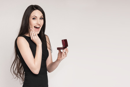 Surprised beautiful woman holding jewelry box with an engagement ring in it. Happy young woman after marriage proposal. White background.
