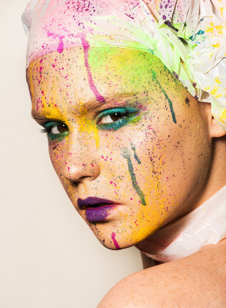 Close-up portrait of young woman with unusual makeup. Model posing with paint drops over her face. Creative makeup. Stock Photo