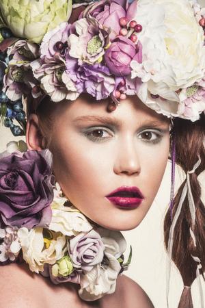 彼女の髪に花を持つ若い魅力的な女性のファッションの肖像画。カメラを見ています。