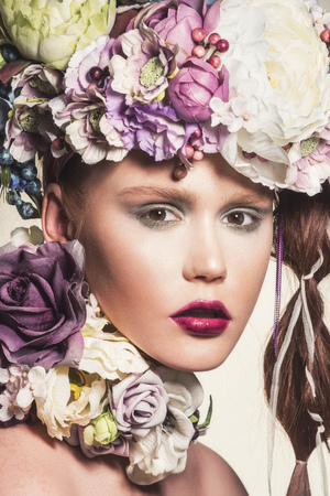 Fashion portrait of young attractive woman with flowers in her hair. Looking at camera. Standard-Bild