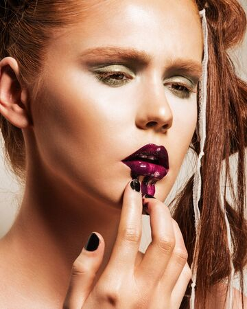 lipgloss: Portrait of young woman wearing vogue style makeup. Beautiful full lips with too much lipgloss applied