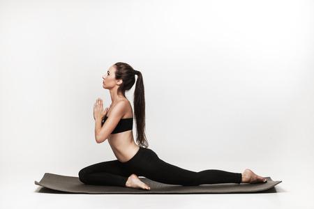 Jonge geschikte vrouw in yogales. Aantrekkelijke donkerbruine vrouw met poneystaart het beoefenen van yoga. Gezonde leefstijl en sport concept. Series van de oefening poses. Geïsoleerd op wit. Stockfoto - 43009902