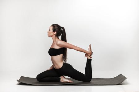 Jonge geschikte vrouw in yogales. Aantrekkelijke donkerbruine vrouw met poneystaart het beoefenen van yoga. Gezonde leefstijl en sport concept. Series van de oefening poses. Geïsoleerd op wit. Stockfoto - 43009904