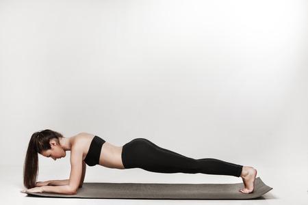 femme brune sexy: Jeune femme de l'exercice. Monter brune sportive faire une planche sur le tapis de yoga. Mode de vie sain et le concept de sport. Série de poses exercice. Isolé sur blanc.