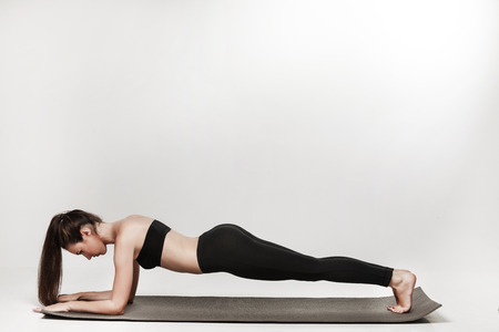 Young woman exercising. Fit sporty brunette doing a plank on yoga mat. Healthy lifestyle and sports concept. Series of exercise poses. Isolated on white.