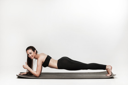 pilates studio: Young woman exercising. Fit sporty brunette doing a plank on yoga mat. Healthy lifestyle and sports concept. Series of exercise poses. Isolated on white.
