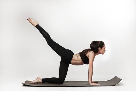 motion: Porträtt av ung attraktiv kvinna gör övningar. Brunett med vältränad kropp på yogamattan. Hälsosam livsstil och sport koncept. Serie av tränings poser. Isolerade på vitt. Stockfoto