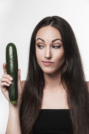 Funny portrait of young brunette woman holding zucchini. Healthy eating lifestyle and weight loss concept.  Studio white background.