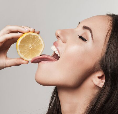 licking tongue: Portrait of woman promoting healthy eating. Beautiful young brunette woman holding fresh sliced lemon. Healthy eating lifestyle and weight loss concept.  Studio white background.