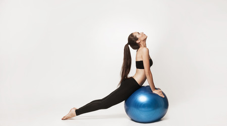 pilates studio: Portrait of young attractive woman doing exercises. Brunette with fit body holding fitness ball. Series of exercise poses. Stock Photo