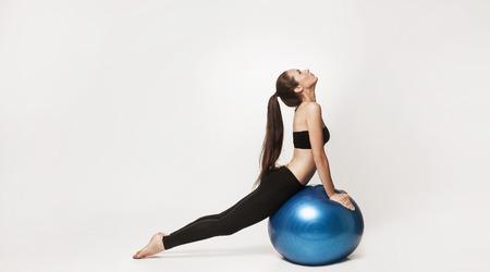 Retrato de mujer haciendo ejercicios de atractivos jóvenes. Brunette con el cuerpo en forma sosteniendo pelota de fitness. Serie de poses de ejercicio.