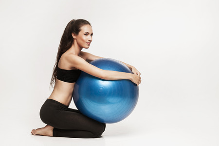 Portrait of young attractive woman doing exercises. Brunette with fit body holding fitness ball. Series of exercise poses. Standard-Bild
