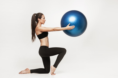 Portrait of young attractive woman doing exercises. Brunette with fit body holding fitness ball. Series of exercise poses. Imagens