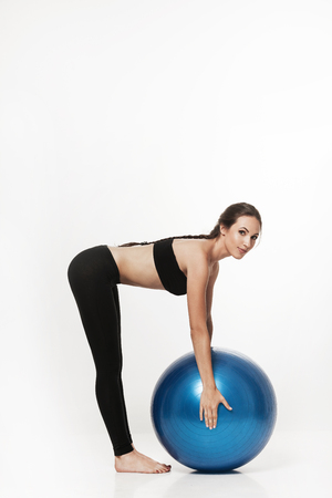 bra: Portrait of young attractive woman doing exercises. Brunette with fit body holding fitness ball. Series of exercise poses. Stock Photo