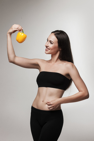 sports bra: Image of woman showing bell pepper. Beautiful young brunette woman with slim body looking at vegetable. Healthy eating and weight loss concept.  Studio white background. Stock Photo