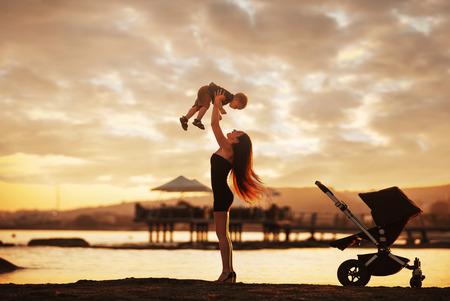 madre e hijo: atractiva madre joven y su bebé que se divierte en la puesta del sol en la playa. Foto de archivo