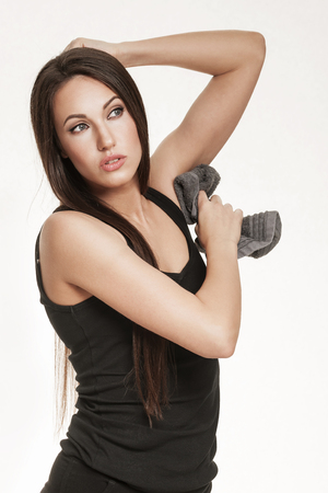underarm: Portrait of good looking brunette woman in sports outfit. Fit woman wiping her underarm pits with towel.