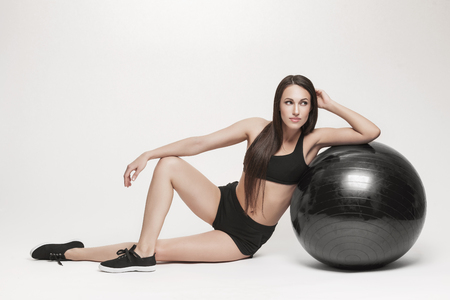 Portrait of young attractive woman doing exercises. Brunette with fit body exercising with fitness ball. Series of exercise poses. Standard-Bild