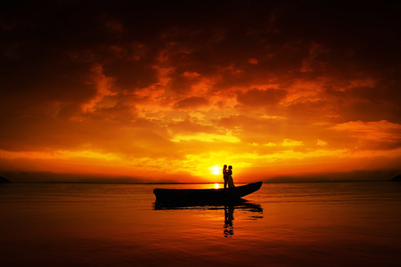 Silhouette of a couple in love. Young people in boat on river in sunset, beautiful skyes. Standard-Bild