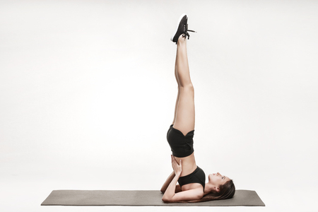 Portrait of young attractive woman doing shoulder stand. Brunette with fit body on yoga mat. Healthy lifestyle  concept. Series of exercise poses.