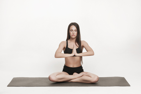 Portrait of young attractive woman doing yoga. Brunette with fit body on yoga mat. Healthy lifestyle and sports concept. Series of exercise poses.